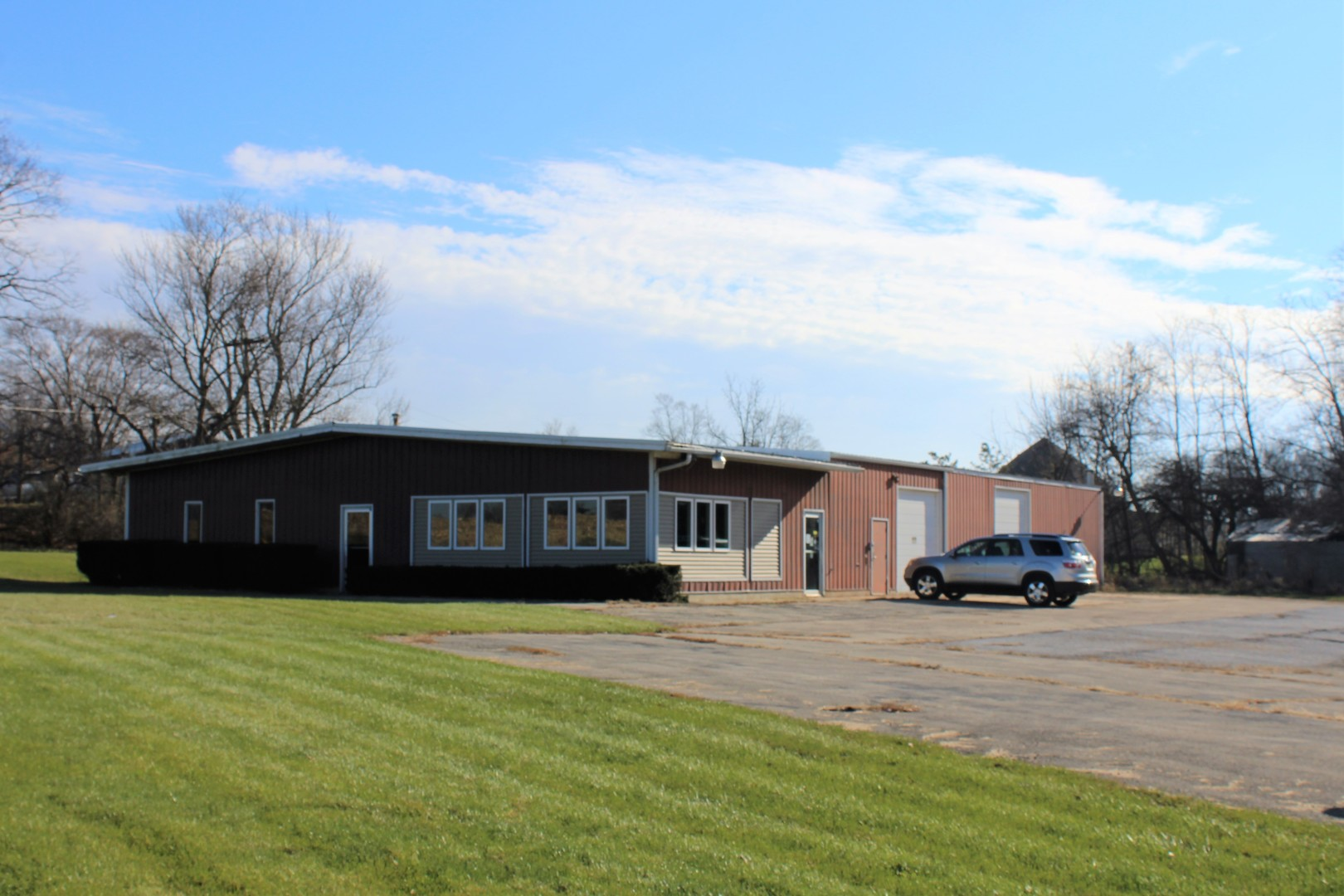 Lots of Potential on 3 */- acres!  The 1978 building is 6000 square feet on a poured foundation with lumber from Rylander, Wisconsin, offering  2 x 10 rafters and 2 x 6 walls. The office / sales area is 30' x 60' with 2: 1/2 baths.  There is a 30' x 30' basement under part of this with 9' ceilings.  A slider door opens from the shop area, so the cars could get to the show room floor.    The 70' x 60' heated shop has 2 hoists and an underground exhaust system, parts room and 1/2 bath.   The drainage system is above ground, commercial septic system, no buried fuel tanks, 3 garage doors, one allows room for a motor home. This flexible property was built for an auto dealership, but can also suit  your needs!  The building was constructed so it could be added on to.   Additionally, there is a cement foundation 30' x 100' with a loading dock  On the west end, south of the existing building. Traffic Count per IDOT 6950 per day.  Check out the aerial photos!